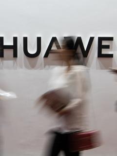 Personas frente al logo de Huawei