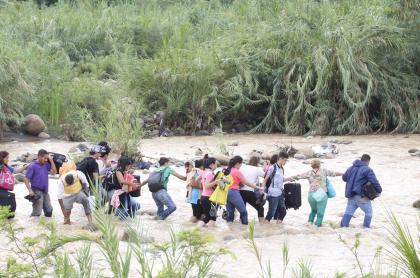 Venezolanos cruzando el río Táchitra hacia Colombia