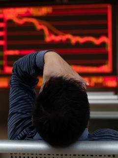 Persona frente a pantallas en bolsa de valores
