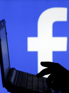 Hombre con un computador y fondo de Facebook
