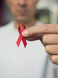 Hombre sosteniendo lazo rojo que representa el VIH