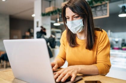 Imagen de referencia de mujer con tapabocas en un computador