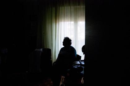 Mujer sola en su casa oscura.