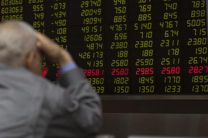 Hombre frente a tablero de valores de bolsa