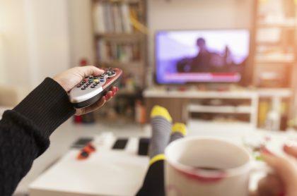 Persona viendo televisión con control remoto en mano