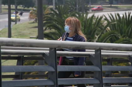 Mujer con tapabocas caminando por Bogotá.