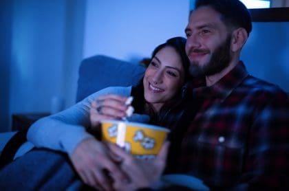 Hombre y mujer viendo televisión, cine
