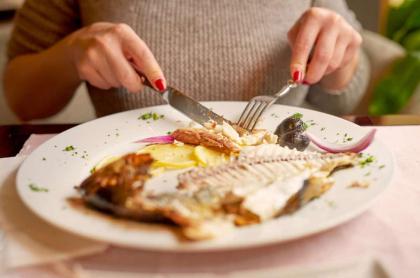 Mujer comiendo pescado.