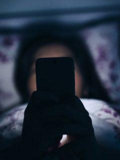 Joven acostada con celular
