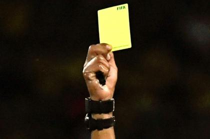 Árbitro con tarjeta amarilla
