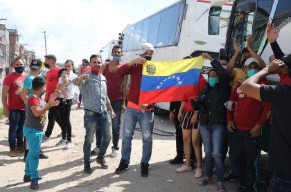 Venezolanos junto a los buses que rentaron para regresar a su país ante emergencia por COVID-19 en Colombia.