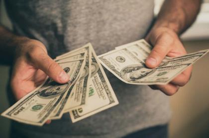 Hombre contando dólares.