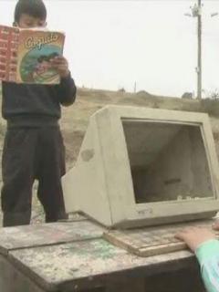 Niños jugando con computador dañado.