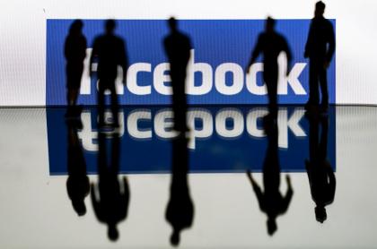 Siluetas de personas sobre logo de Facebook