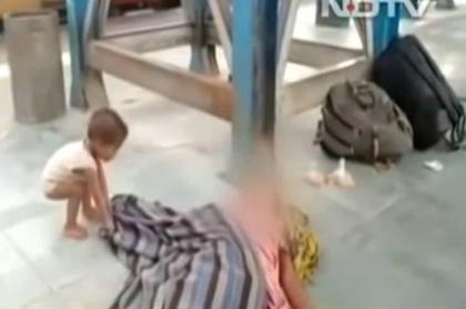 Niño que trata de despertar a su madre muerta, en India