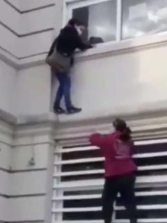 Mujer trepada en pared.