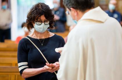 Sacerdote haciendo misa y dando la comunión durante la pandemia de COVID-19