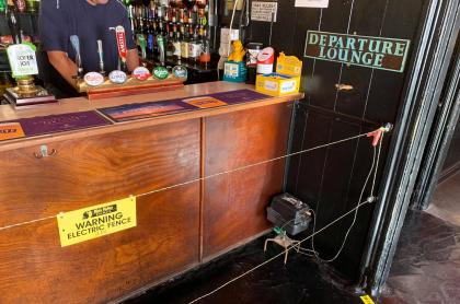 Bar instaló valla eléctrica entre la barra y los clientes para mantener el distanciamiento.