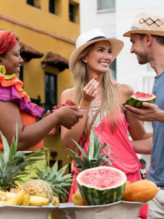 Pareja de turistas comprando frutas a una palenquera en Cartagena.