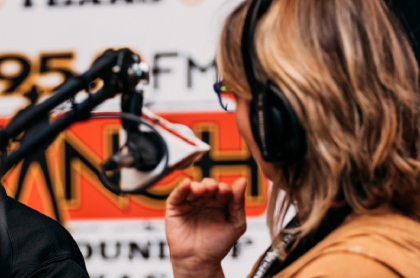 Mujer con audífonos frente a micrófonos