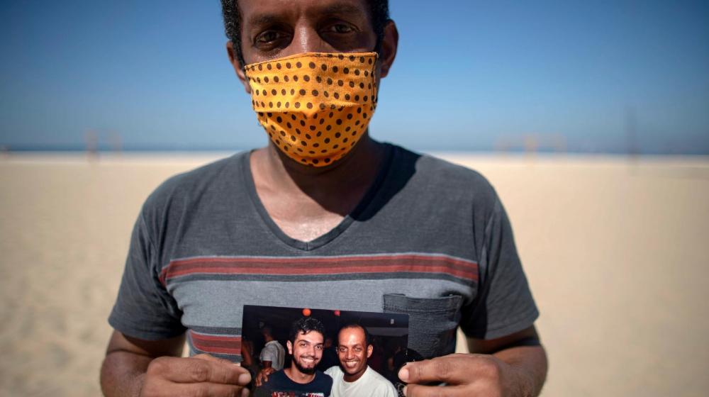 Foto de brasileño posando con foto de su familiar fallecido por coronavirus en la playa Copacabana.