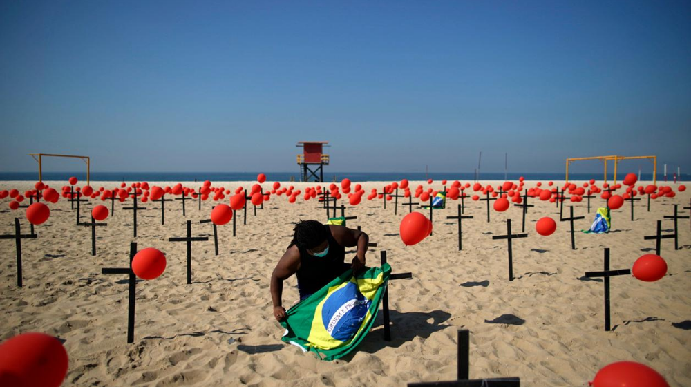 Brasileño colocando bandera de brasil en playa de Copacabana.