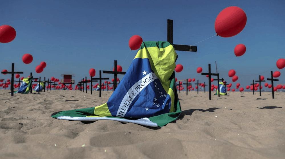 Bandera de Brasil fijada sobre una cruz negra en medio de la playa de Copacaba en Brasil.