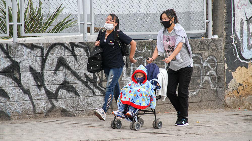 En el sector de Corabastos dos mujeres caminan, llevan en un coche para bebé a un niño.