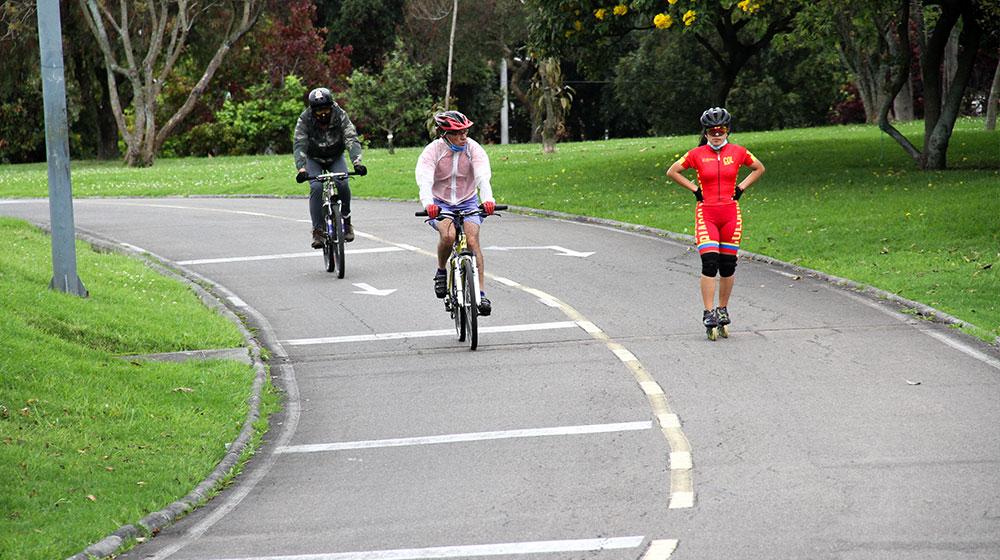 Dos hombres en bicicleta y una joven en patines realizando ejercicio en los alrededores de la Biblioteca Pública Virgilio Barco.