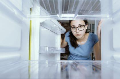 Imagen una mujer mirando la nevera vacía ilustra nota de encuesta del Dane