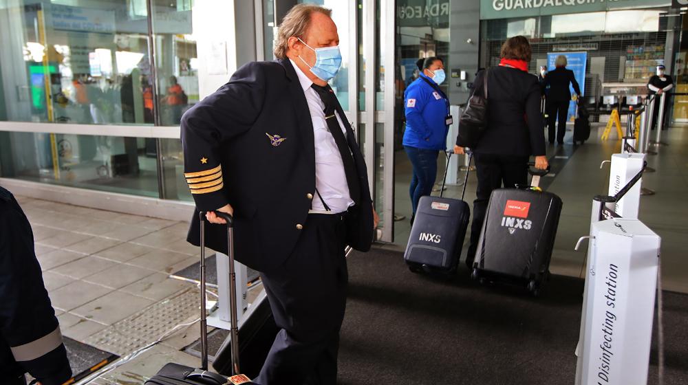 Piloto con tapabocas llegando al Aeropuerto Internacional El Dorado