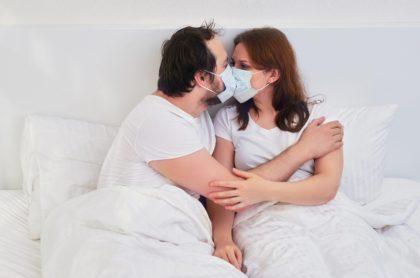 Pareja en una cama se 'besa' con tapabocas, ilustra nota de recomendación de usar mascarilla durante el sexo