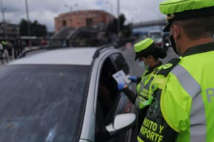 Policía revisando documentos de conductor, en Bogotá. Conozca las infracciones y las multas que pueden ponerle si incumple normas de tránsito.