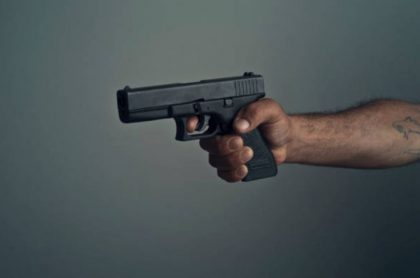 Hombre sostiene pistola, ilustra nota de joven que fue asesinado por hombre que lo violó