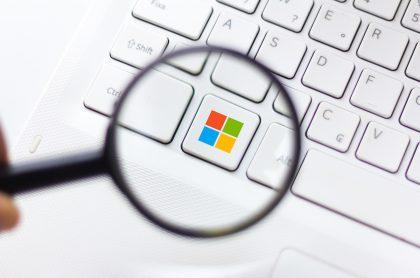 Logotipo de Microsoft bajo una lupa para ilustrar nota sobre la herramienta creada para detectar 'deepfakes'