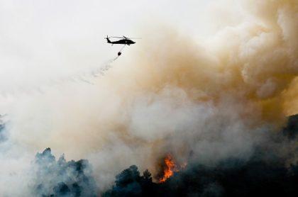 Helicóptero en medio de incendio, que ilustra nota de rescate en California, EEUU