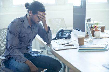 Imagen de hombre estresado en oficina, que ilustra nota sobre el salario promedio en Colombia