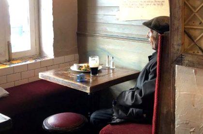 Adulto mayor toma cerveza en un pub irlandés.