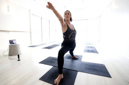 Mujer haciendo yoga en casa, ilustra nota de yoga para principiantes.