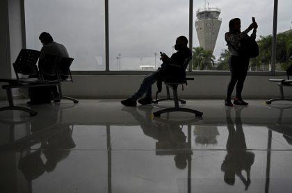 El primer vuelo internacional que saldrá de Colombia en medio de la crisis por COVID-19 tendrá como destino la ciudad de Miami, Estados Unidos. Personas sentadas en aeropuerto.
