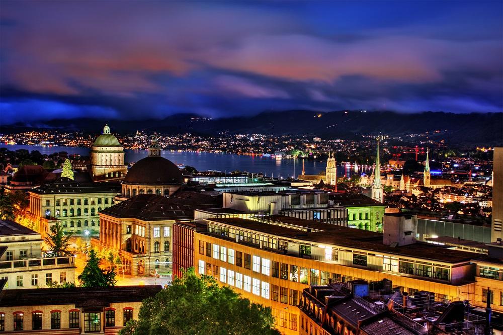 Vista nocturna de Zúrich, Suiza, con los 2 edificios principales de la Universidad y la Escuela Politécnica Federal de Zúrich, instituciones a las que colombianos pueden aplicar a becas.