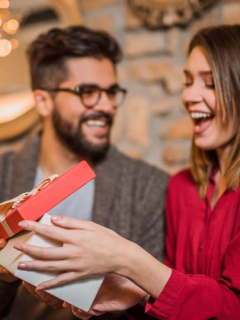 Mujer abre regalo que le dio su pareja, a propósito del día de amor y amistad, y los regalos que se pueden obsequiar en esa fecha
