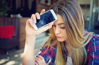 Imagen de mujer preocupada porque su celular se dañó para ilustrar nota sobre los elementos aparentemente inofensivos que pueden dañar el móvil
