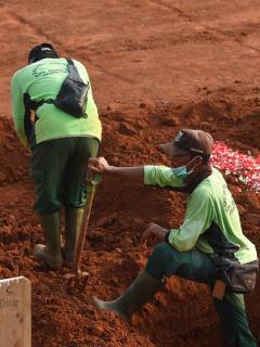 Sepultureros cavando tumbas para los fallecidos por COVID-19 en indonesia.