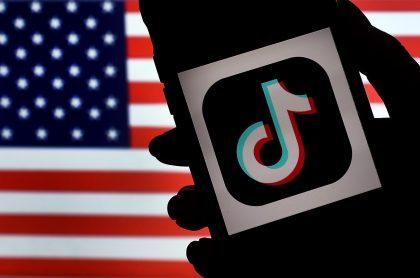Logo de TikTok sobre bandera de Estados Unidos ilustra artículo Prohibidas aplicaciones chinas TikTok y WeChat en EE.UU.
