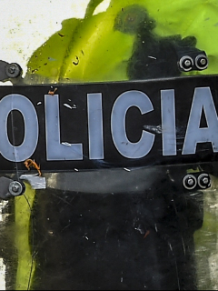 """(FILES) In this file picture taken on September 9, 2020 riot police stand guard during a protest against the death of a lawyer under police custody, in Bogota. - Colombian prosecutors on September 18, 2020 charged two police officers with torture and aggravated homicide after the death of a man in custody sparked deadly rioting in the capital and other cities. The two police involved in the arrest of Javier Ordonez, who was repeatedly tasered before dying later in custody, were charged with """"torture and aggravated homicide,"""" prosecutor's office official Francisco Barbosa said. Five other police officers are under investigation in the case. (Photo by Juan BARRETO / AFP)"""