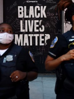 Letrero de Black Lives Matter detrás de policías de Nueva York.