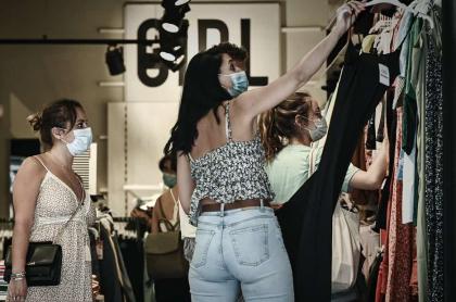 Imagen con clientas que miran ropa en tienda durante las rebajas en Burdeos, Francia, en julio de 2020, ilustra artículo sobre tercer Día sin IVA en Colombia.
