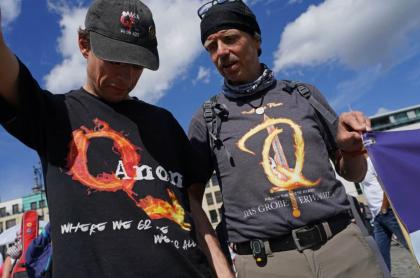 Dos estadounidenses lucen camisetas de Qnon, un movimiento conspirativo que endiosa a Donald Trump.