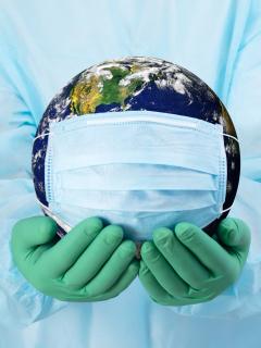 Manos de médico con guantes que sostienen el planeta Tierra con un tapabocas. Foto de referencia para ilustrar que el mundo superó el millón de muertes por COVID-19.